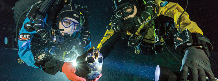 Photograph of two divers. One 的 the divers is holding a human skull.