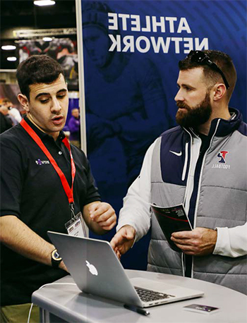 Ben Weiss selling technology at a convention to a bearded man.