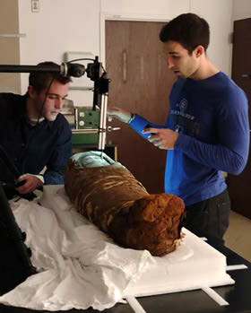Two scientists examine the mummy 和 wrappings.